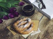 Todavía vida con los tulipanes, el libro, el café y el pretzel en fondo de madera Foto de archivo