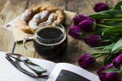 Todavía vida con los tulipanes, el libro, el café y el pretzel en viejo fondo Fotos de archivo