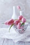 Todavía vida con los tulipanes rosados en una taza de té Imágenes de archivo libres de regalías