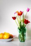 Todavía vida con los tulipanes y las frutas Foto de archivo