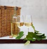 Todavía vida con los vidrios de vino blanco, botella, cesta Fotos de archivo libres de regalías