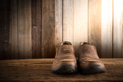 Todavía vida con los zapatos de los hombres en el tablero de la mesa de madera contra wa del grunge Imagenes de archivo