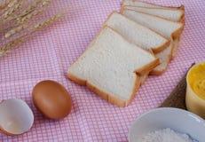 Todavía vida con pan, el huevo, la harina, el magarine y el trigo cortados en etiqueta Fotografía de archivo