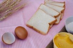 Todavía vida con pan, el huevo, la harina, el magarine y el trigo cortados en etiqueta Fotos de archivo libres de regalías