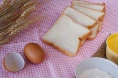 Todavía vida con pan, el huevo, la harina, el magarine y el trigo cortados en etiqueta Foto de archivo libre de regalías