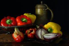Todavía vida con pimientas, cebollas y un jarro de bronce Fotografía de archivo