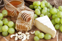 Todavía vida con queso, la uva y la miel Fotos de archivo