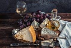 Todavía vida con queso Maasdamer del queso, brie, camembert, vinograd, MED fotos de archivo libres de regalías