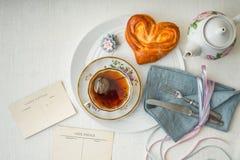 Todavía vida con té y el bollo del amor en la opinión de sobremesa blanca Fotografía de archivo libre de regalías