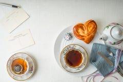 Todavía vida con té y el bollo del amor en la tabla blanca horizontal Fotos de archivo libres de regalías
