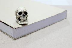 Todavía vida con un cráneo y un libro en la tabla de madera Foto de archivo libre de regalías