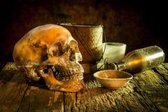 Todavía vida con un cráneo y una taza, vidrio, botella, arroz del kratib en de madera Fotografía de archivo libre de regalías