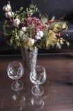 Todavía vida con un florero de plata y un ramo brillante y dos copas de vino Fotos de archivo libres de regalías