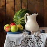 Todavía vida con un jarro blanco, manzanas y una sandía Foto de archivo