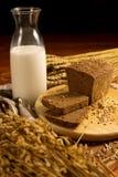Todavía vida con un jarro de cristal de leche, pan de centeno, espigas de trigo Imágenes de archivo libres de regalías