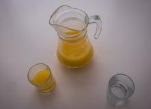 Todavía vida con un jarro, dos vidrios y zumo de naranja Imagenes de archivo