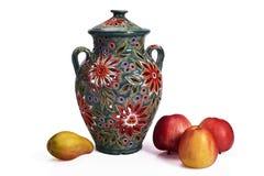 Todavía vida con un jarro hecho a mano de cerámica colorido, las manzanas y la pera Fotos de archivo libres de regalías