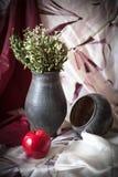 Todavía vida con un jarro negro y una manzana roja Foto de archivo libre de regalías