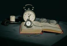 Todavía vida con un libro y los relojes en colores oscuros Foto de archivo libre de regalías