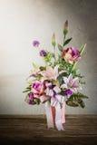 Todavía vida con un manojo de flores hermoso con la telaraña en la madera Imagen de archivo