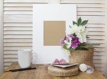 todavía vida con un marco blanco, la taza y una flor agradable Foto de archivo libre de regalías