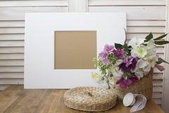 Todavía vida con un marco blanco y flores agradables Imagen de archivo libre de regalías