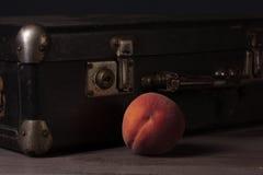 Todavía vida con un paquete y los melocotones Foto de archivo libre de regalías