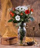 Todavía vida con un ramo de flores, de un libro y de una palmatoria Imagen de archivo