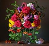 Todavía vida con un ramo de flores y de bayas del jardín Imagenes de archivo