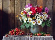 Todavía vida con un ramo de flores y de fresas del jardín Foto de archivo libre de regalías