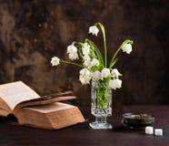 Todavía vida con un ramo de flores y de un libro Fotos de archivo libres de regalías