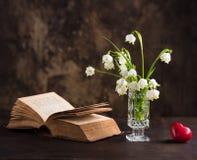 Todavía vida con un ramo de flores y de un libro Foto de archivo libre de regalías