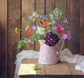 Todavía vida con un ramo del verano en la tabla de los tableros Fotos de archivo libres de regalías