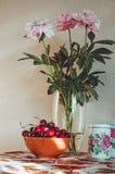 Todavía vida con un ramo fresco del manojo de las peonías blancas, rosadas en el florero de cristal, cerezas oscuras en la tabla, Imágenes de archivo libres de regalías