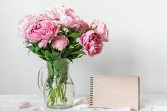 Todavía vida con un ramo hermoso de flores rosadas de la peonía y de cuaderno de papel en blanco Mofa para arriba Fondo del día d imagen de archivo libre de regalías