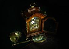Todavía vida con un reloj de tabla, una lupa, una campana y un libro viejo Foto de archivo