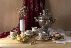 Todavía vida con un samovar, un té, galletas y tortas en un primer de madera de la tabla Imágenes de archivo libres de regalías
