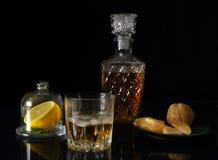 Todavía vida con un vidrio del whisky y del limón Fotos de archivo