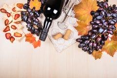 Todavía vida con una botella y un vidrio de vino rojo, de uvas y de chocolate con las fresas Fotografía de archivo libre de regalías