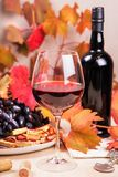 Todavía vida con una botella y un vidrio de vino rojo, de uvas y de chocolate con las fresas Imagen de archivo