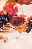 Todavía vida con una botella y un vidrio de vino rojo, de uvas y de chocolate con las fresas Imagenes de archivo
