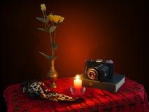Todavía vida con una cámara y un libro viejos de la vela Imagen de archivo libre de regalías