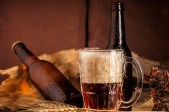 Todavía vida con una cerveza de barril por el vidrio en la tabla de madera Imagenes de archivo