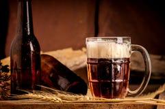 Todavía vida con una cerveza de barril por el vidrio en la tabla de madera Fotografía de archivo