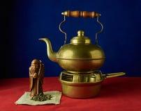 Todavía vida con una figurilla del té de dios, del té verde y del ol Foto de archivo