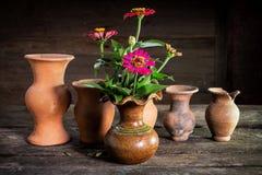Todavía vida con una flor del florero, loza de barro Foto de archivo