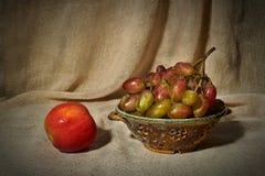 Todavía vida con una manzana, uvas y un colador Imágenes de archivo libres de regalías