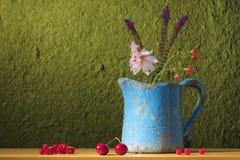 Todavía vida con una poder, las flores y la fruta Foto de archivo libre de regalías