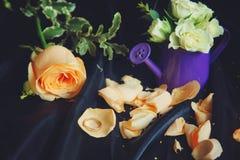Todavía vida con una regadera púrpura y las flores, anillo de bodas en los pétalos color de rosa Foto de archivo libre de regalías