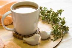 Todavía vida con una taza de café y de flores en una tabla de madera del color crema ligero con dos pájaros de cerámica Hogar aco Foto de archivo